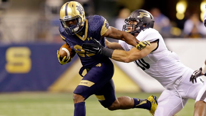 Notre Dame running back Tarean Folston, left, sheds the tackle of Purdue linebacker Sean Robinson during the second half of an NCAA college football game in Indianapolis, Saturday, Sept. 13, 2014. (AP Photo/Michael Conroy)