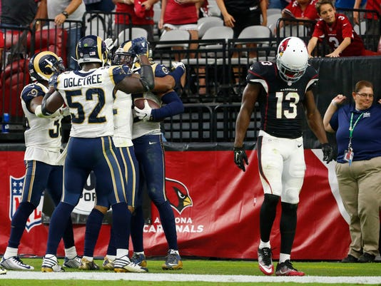 Arizona Cardinals wide receiver Jaron Brown (13) looks down after Los Angeles Rams strong safety T.J. McDonald (25) intercepted a pass in the end zone during an NFL football game in Glendale, Ariz., Sunday, Oct. 2, 2016. The Rams won 17-13. (Michael Chow/The Arizona Republic via AP)