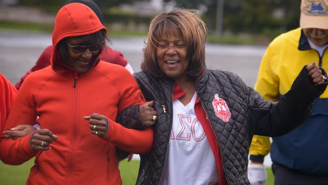 Delta Sigma Theta Sorority alumnae Patricia Stevens, left, and Brenda Murphy-Pough, right, do a warm-up routine before the alumnae group's 5K fundraiser on Saturday, Oct. 3, 2015.