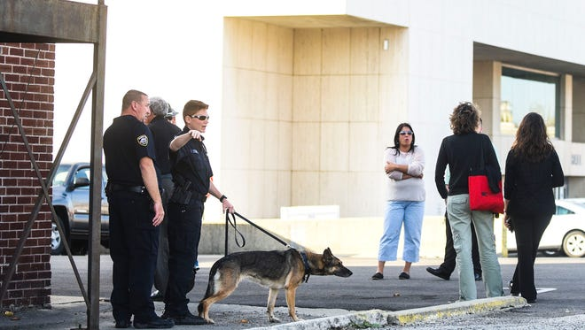 Officers discuss the situation of a suspicious package found in City Hall on Tuesday afternoon. City Hall was evacuated and federal bomb squad officials were called into investigate and clear the building.