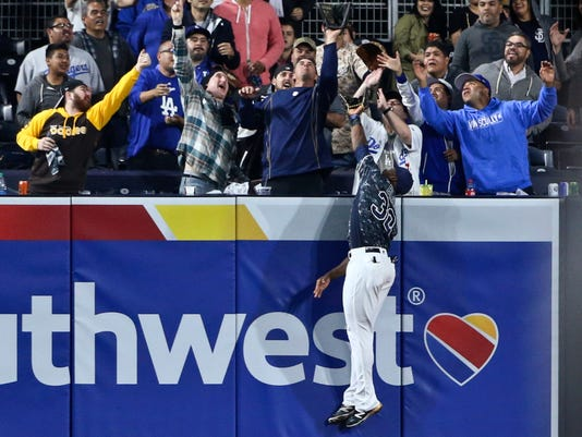 San Diego Padres left fielder Jabari Blash leaps at the wall but cannot catch a home run hit by Los Angeles Dodgers' Yasiel Puig during the eighth inning of a baseball game Wednesday, April 6, 2016, in San Diego. (AP Photo/Lenny Ignelzi)
