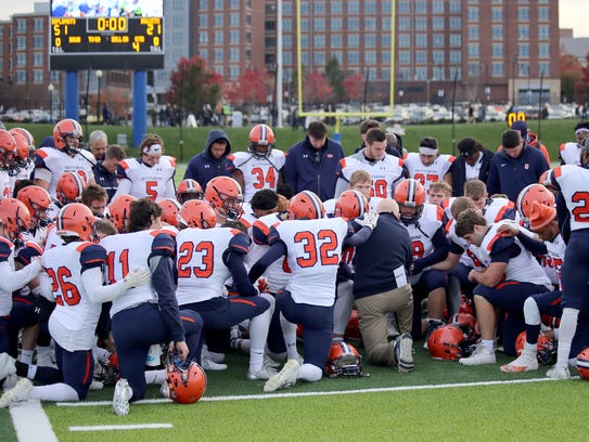 The Gettysburg football team prays together after the