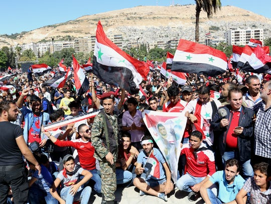 Syrians wave the national flag as they watch on a screen