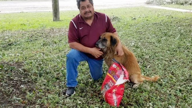 Salvador Segovia and Otis pose outside Segovia's home in Stinton, Texas, on Saturday. Otis, who belongs to Segovia's grandson, was seen walking on the street after the storm and carrying the bag of dog food.