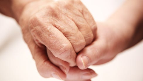 A stock image of two people holding hands.