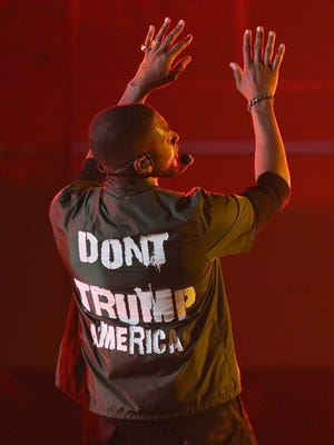 Usher performs at the BET Awards in a statement jacket.