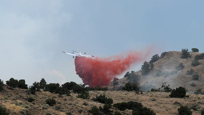 Crews work to put out a small brush fire near Spanish Springs High School and Hungry Valley north of Reno on Aug. 17, 2016.