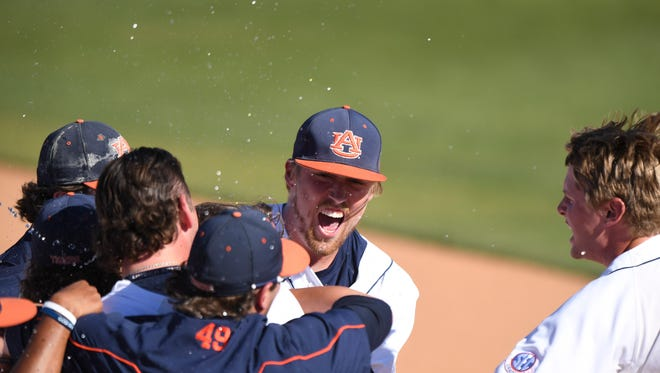 Daniel Robert (20) and Cole Lipscomb (49) celebrate with teammates after Auburn baseball completes a 3-game sweep of Florida on Sunday, March 19, 2017 in Auburn, Ala.
