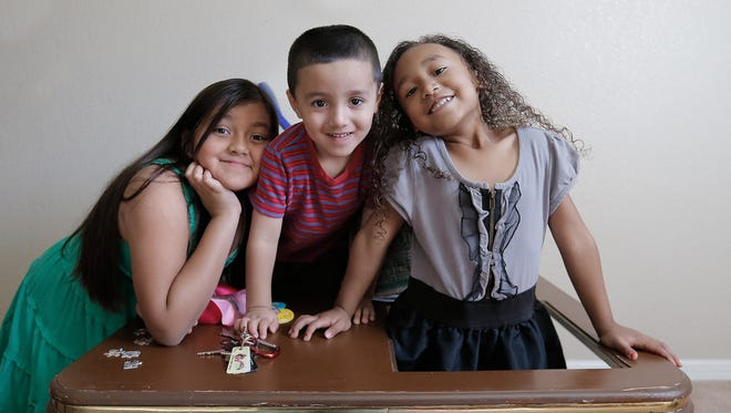 Cassandra, 9, left, Sebastian, 4, center, and Melanie, 5, play in the family's living room as people show up at their apartment with donations through Operation Noel.