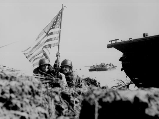 Two U.S. officers plant the American flag on Guam eight minutes after U.S. Marines and Army assault troops landed on the Central Pacific island on July 21, 1944.