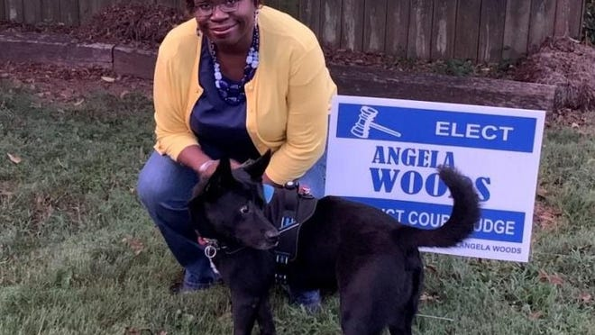 Angela Woods and her sister's dog, Judah, pose for a photograph near a campaign sign. Woods, of Kings Mountain, is running for a judge's seat on the District Court bench to represent Cleveland and Lincoln counties.