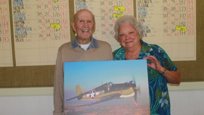 Bill Heck, left, poses with his wife Audrey Heck, and a canvas photo of a Hellcat plane flown during World War II. The photo was a gift from La Playa Golf Club members. Heck's worked at the country club since 2003 as a starter, and flew a Hellcat during World War II.