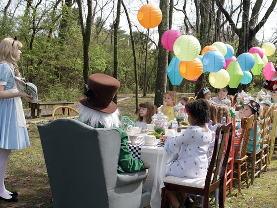 Alice reads her story to kids at the tea party at the