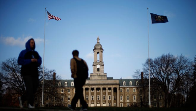 Two male students walk past the Old Main building on the Penn State campus.