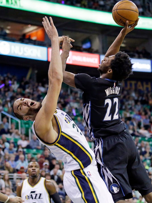 Minnesota Timberwolves guard Andrew Wiggins (22) goes to the basket as Utah Jazz center Rudy Gobert, left, defends during the first quarter of an NBA basketball game Friday, April 1, 2016, in Salt Lake City. (AP Photo/Rick Bowmer)