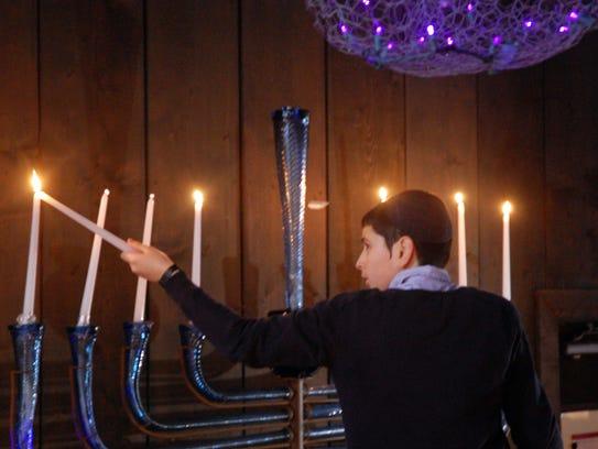 Avi Rapoport, 13, of Vineland, lights a glass menorah