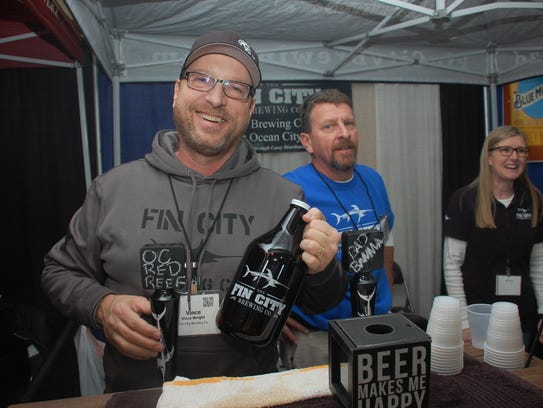 Vinnie Wright poses for a photo while filling a growler.