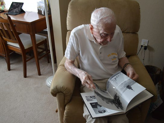 Joseph Vogel, a 94-year-old World War II U.S. Navy veteran, sifts through a 50th anniversary book about the Destroyer he was on during World War II -- the USS Ordronaux (DD-617) -- in his SouthWood apartment Wednesday morning. He will go on the Honor Flight Tallahassee with other veterans, and with his daughter as his guardian, on May 19.