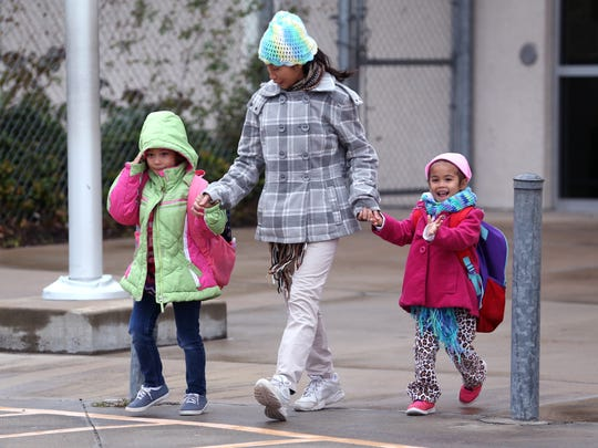 Huapen Serna, 5 (from left), Annabelle Serna, and Amanda Serna, 4, head to their car as at Evans Elementary School on Tuesday, Jan. 16, 2018. School was released early due to expected bad weather.