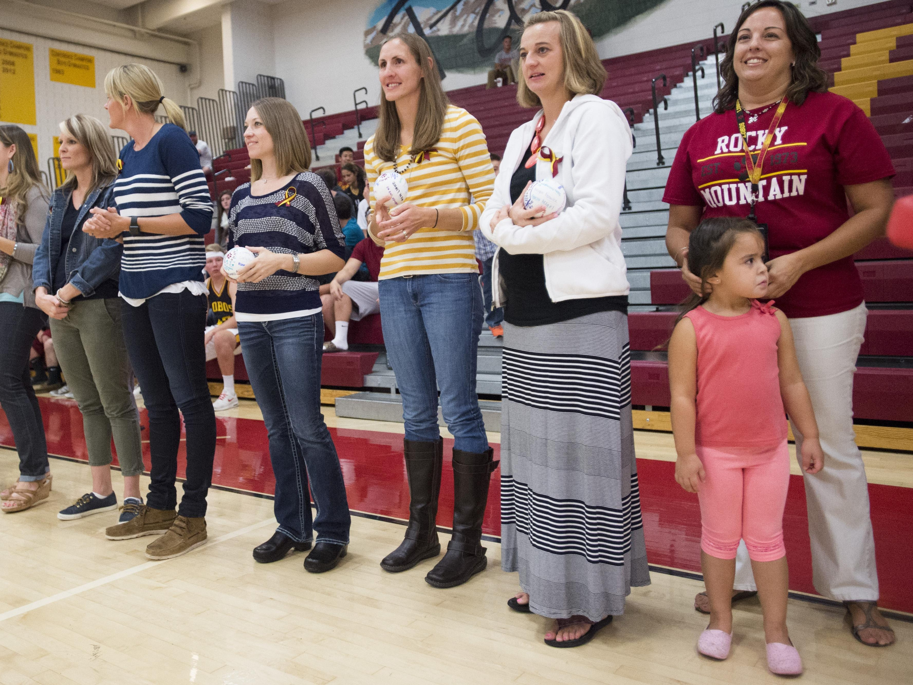 Members of the 1995 and 1999 Rocky Mountain High School volleyball state title teams are honored before the third set in a game against Mountain Range Tuesday.