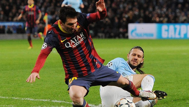 FC Barcelona's Lionel Messi, left, is fouled in the penalty box by Manchester City's Martin Demichelis during the UEFA Champions League round of sixteen first leg soccer match between Manchester City and FC Barcelona at the Etihad Stadium in Manchester, Britain.