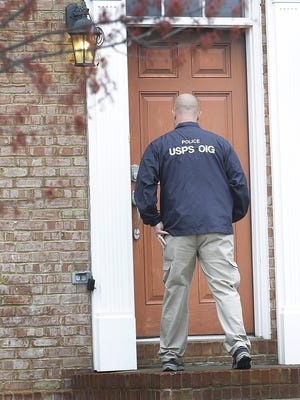 A federal agent from the U.S. Postal Service Office of Inspector General enters the home at 2400 block of Buckland Street in the Village of West Clay in Carmel on Thursday, March 31, 2016. Agents from the FBI were also on the scene.