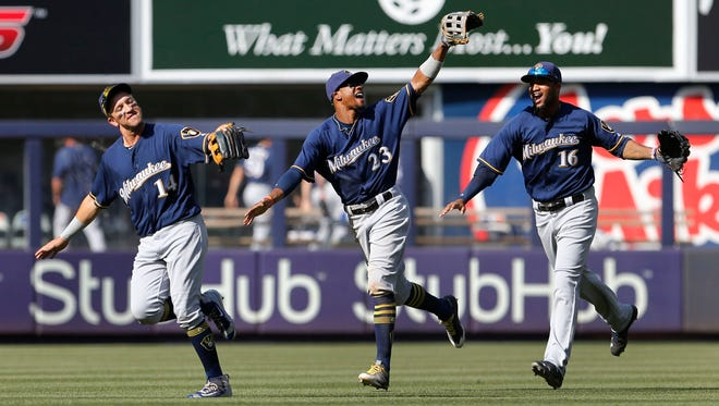 """Hernan Perez (from left), Keon Broxton and Domingo Santana celebrate after the Brewers beat the Yankees on Sunday. Despite being together for just a short time, the young Brewers have developed into a tight-knit group. """"We enjoy each other's company,"""" manager Craig Counsell said."""