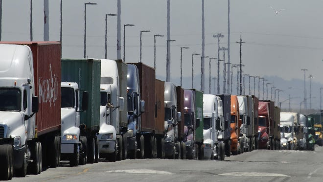 In this July 22, 2019 photo, trucks hauling shipping containers wait to unload at the Port of Oakland in Oakland, Calif.  The Commerce Department issues its second estimate of how the U.S. economy performed in the first quarter of 2020 on Thursday, May 28, 2020.