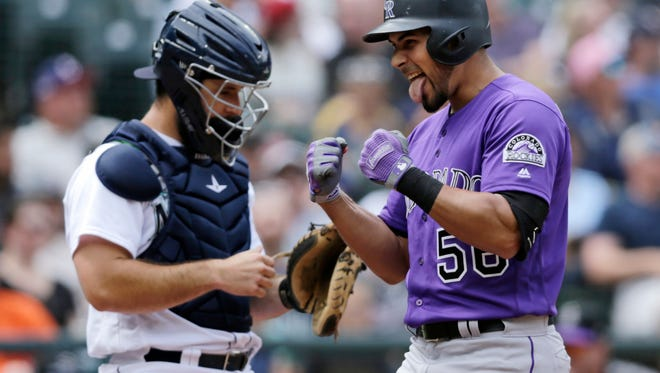Colorado Rockies' Noel Cuevas, right, celebrates as he reaches home after hitting a three-run home run on a pitch from Seattle Mariners starter James Paxton during the seventh inning of a baseball game, Saturday, July 7, 2018, in Seattle. (AP Photo/John Froschauer)