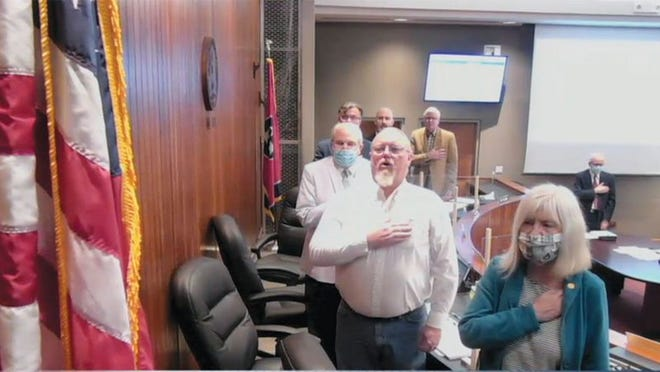 This screenshot shows Oak Ridge City Council saluting the American flag at the beginning of its first in-person meeting in many weeks. Council members have been meeting via video conferencing software. The Council meets in the Municipal Building courtroom. Meetings are still streamed for people wishing to view them. Pictured from front to back are Council members Kelly Callison and Jim Dodson, Mayor Pro Tem Rick Chinn, Mayor Warren Gooch and City Council member Chuck Hope and Ellen Smith. To the right is city attorney Ken Krushinski.