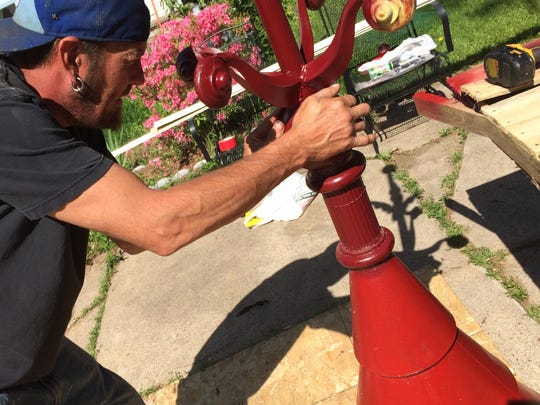 K.C. Dreiling of Excellence in Home Renovation works on restoring the finial that will be placed on top of the home's tower.