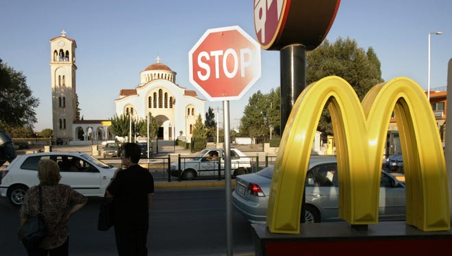 In this Aug. 19, 2004 file photo, commuters stand near a McDonald's restaurant in Marathon, Greece.