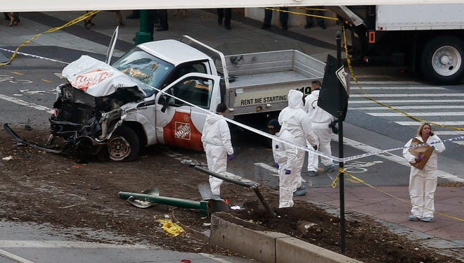 Authorities stand near a damaged Home Depot truck after a motorist drove onto a bike path near the World Trade Center memorial, striking and killing several people on Oct. 31, 2017, in New York.