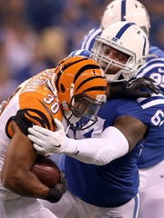 Indianapolis Colts defensive end Earl Okine (64) hits Cincinnati Bengals running back Cedric Peerman (30) in the first half of their preseason game Thursday, September 3, 2015, at Lucas Oil Stadium.