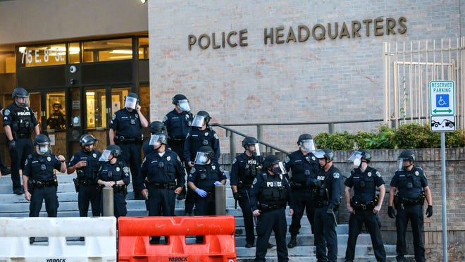 Austin Police officers stand in front of the APD headquarters entrance as Black Lives Matter protesters arrive in Austin on June 19.