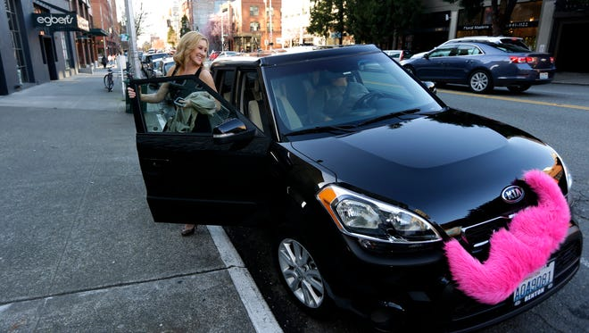 Katie Baranyuk, gets out of a car driven by Dara Jenkins, a driver for the ride-sharing service Lyft, after getting a ride to downtown Seattle to meet friends after work in March.