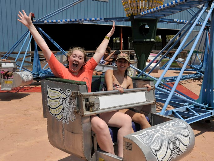 Sierra Stephens, 16, and Shania Beers, 16, ride the Santa Ana Scrambler at Sam's Fun City Wednesday afternoon.