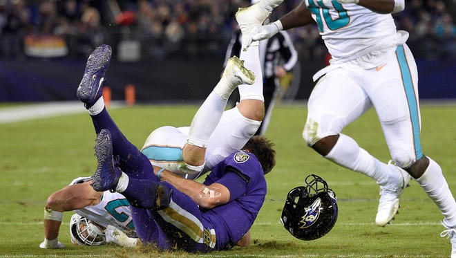 Miami Dolphins middle linebacker Kiko Alonso, top left, collides with Baltimore Ravens quarterback Joe Flacco as Flacco slides on the field after rushing the ball in the first half of an NFL football game, Thursday, Oct. 26, 2017, in Baltimore.