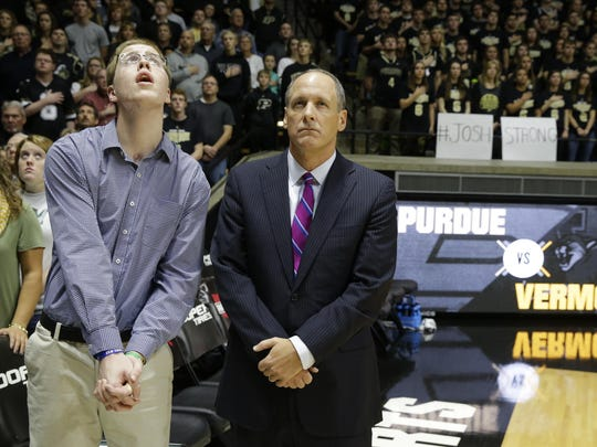 Josh Speidel, left, stands with Vermont head coach John Becker during the national anthem before an NCAA college basketball game against Purdue in West Lafayette, Ind., in November. Speidel is recovering from a Feb. 1 auto accident that resulted in a traumatic brain injury.