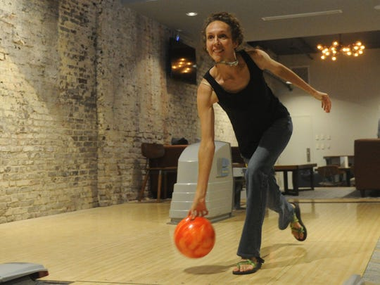 Lauren Lucchesi, of Lauderdale Design Group, which helped design the new Maple Hall bowling ally on 414 S. Gay Street , throws a ball down a lane on Tuesday, June 28, 2016. The bowling ally will open to the public on the June 29. (CAITIE MCMEKIN / NEWS SENTINEL)