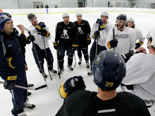 Forner Buffalo Sabres player Andrew Peters, left, and Sabres players talk during a 2013 workout in Amhers. Peters has been suspended indefinitely as coach of a youth hockey team pending a police investigation into his role in an on-ice brawl.