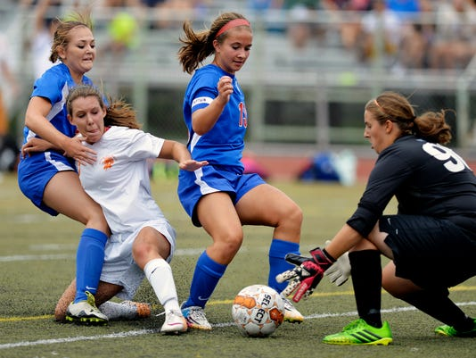 Spring Grove's Kaitlin Dunne makes a save after York Suburban's Abby Eisenhart gets past Ashley Forbes and Leanna Miller in a first-round game in the York Suburban Soccer Tournament on Saturday, Aug. 30, 2014. The Trojans defeated the Rockets 2-1 to move on to the championship game against the York Catholic Fighting Irish. York Suburban hosted York Catholic, Spring Grove and Lancaster Catholic in its fifth annual soccer tournament. Chris Dunn -- Daily Record/Sunday News