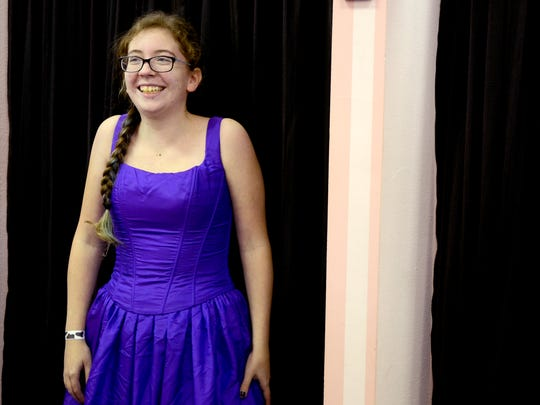 June Wayne, 17, smiles after seeing herself in a purple gown during the SnoBall Formal Wear Giveaway at the Bridal Gallery in downtown Salem on Saturday, Nov. 15, 2014.
