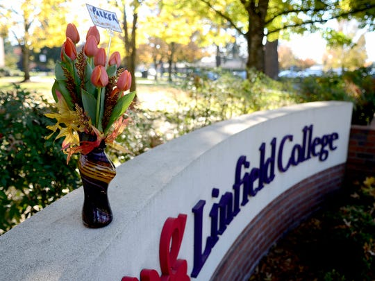 Flowers lay in memory of Parker Moore at Linfield College in McMinnville, Ore., on Sunday, Nov. 16, 2014. Moore, a sophomore, was fatally stabbed Saturday night at a 7-Eleven next to the campus.