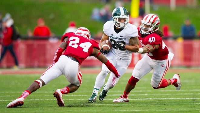 Indiana University redshirt senior Tim Bennett (24) and sophomore Antonio Allen (40) close in on Michigan State University senior Nick Hill (20) as he rushes the ball upfield during the first half of action. Indiana University hosted Michigan State University in Big Ten football action, Saturday, October 18, 2014, in Bloomington, Ind.
