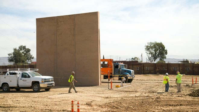 Construction continues of the border wall prototype designed and contracted to Fisher Sand & Gravel of Tempe, among the construction of the prototypes near the Otay Mesa Port of Entry outside of San Diego, California, on Oct. 17, 2017.