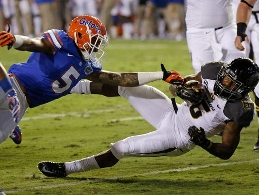 Missouri running back Marcus Murphy, right, slips past Florida defensive back Jalen Tabor (5) for a touchdown on a 5-yard run during the first half of an NCAA college football game in Gainesville, Fla., Saturday, Oct. 18, 2014. (AP Photo/John Raoux)
