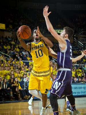 Michigan guard Derrick Walton Jr. (10) tries to go to the basket, defended by Northwestern guard Bryant McIntosh, right, in the second half of an NCAA college basketball game at Crisler Center in Ann Arbor, Mich., Wednesday, Feb. 24, 2016. Michigan won 72-63. (AP Photo/Tony Ding)