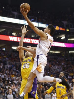 Suns' Devin Booker (1) goes up for a layup against Lakers' Andrew Bogut (66) during the first half on Nov. 13, 2017 at Talking Stick Resort Arena in Phoenix, Ariz.
