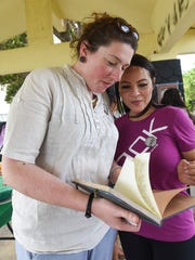 Ramona Siblang, right, reads a message book with long